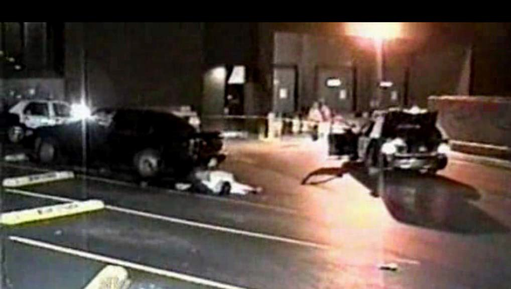 View of crime scene showing victim's car and location of body before removal. This image was also taken before the placement of cones. Still from NBS Dateline video.