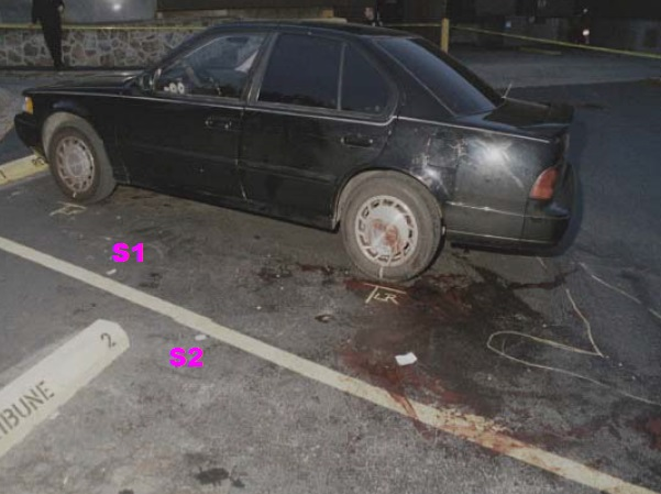 View of crime scene on driver side of Heitholt Maxima after removal of body and loose items on pavement. The chalk outline denotes the relative location of the victim's body before removal. Both wheels have been chalk marked for their position on the pavement in preparation for removal of the vehicle. Note the blood on the pavement and on the left rear wheel rim and cover. S1 locates pavement scuff marks possibly made by the victim during the attack. S2 locates apparent rotational scuff marks possibly made by victim or killer during the attack. Modified Crime scene photo found on CBS news Internet site. Several of the following photos were made prior to this photo.