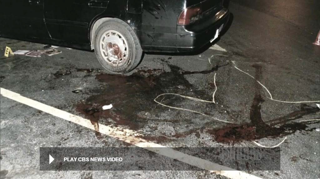 View showing most of the blood markings on the pavement. Video taken after the body was removed. Note the items under the vehicle. The severed belt buckle has already been secured at the time of this video. Still from CBS News video.