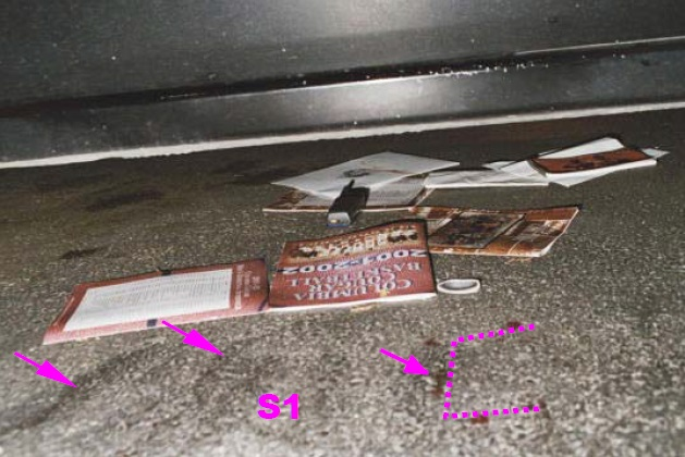 View of several magazine and other paper items found under the Heitholt Maxima. Heitholt's cell phone and right lens of his glasses are also under the car. Note the several pavement scuff marks this side of magazines. These pavement scuff marks were denoted as site S1 in earlier photo. Two of the largest scuff marks are highlighted by the two arrows on the left. Also note blood drops in a near rectangular outline with several on top of the pavement scuff marks. The arrow in the middle of the rectangular outline points to what appears to be several drops in a line. This may also have been a laydown location for the assault weapon. Modified CBS News police photo from Internet.